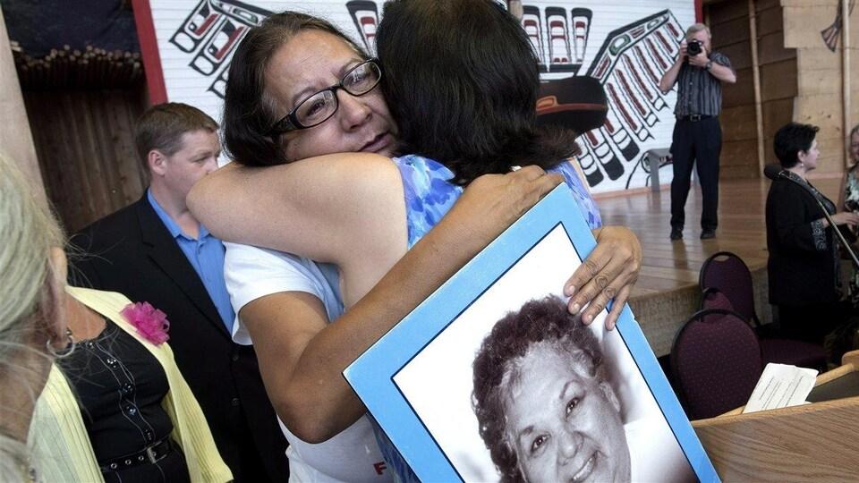 Bridget Tolley pleure après l'annonce sur l'Enquête nationale sur les femmes autochtones. Elle tient une photo de sa mère tuée en 2001.