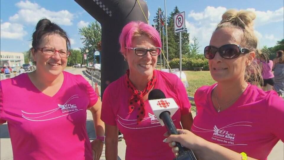 Trois femmes vêtues de rose sourient et répondent à la journaliste.