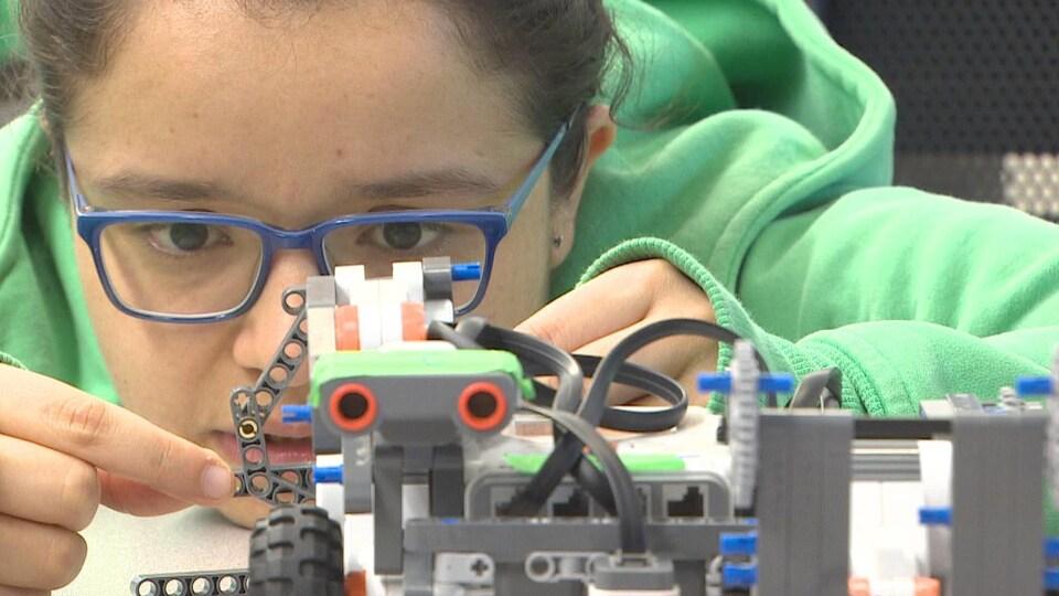Jeune femme travaillant sur un robot.