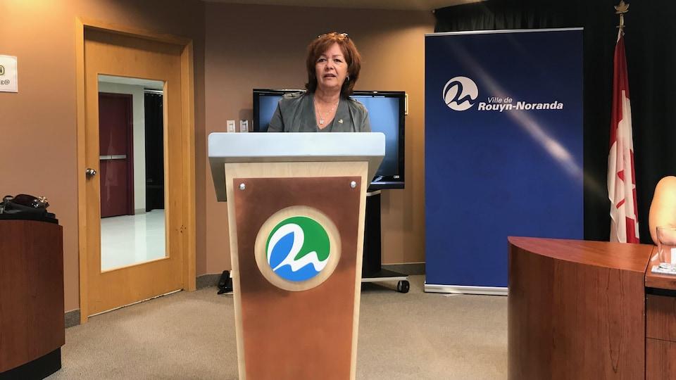 La mairesse de Rouyn-Noranda Diane Dallaire prend la parole devant un lutrin dans la salle du conseil municipal.