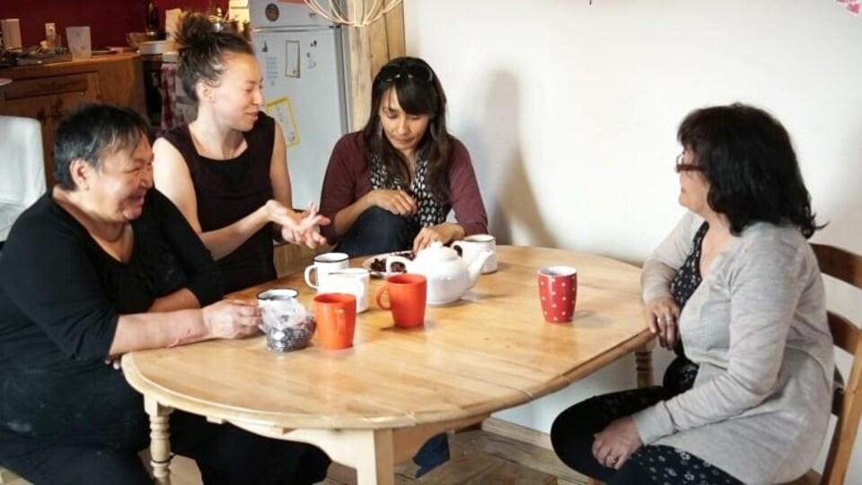 Des femmes autour d'une table discutent en prennant le thé.