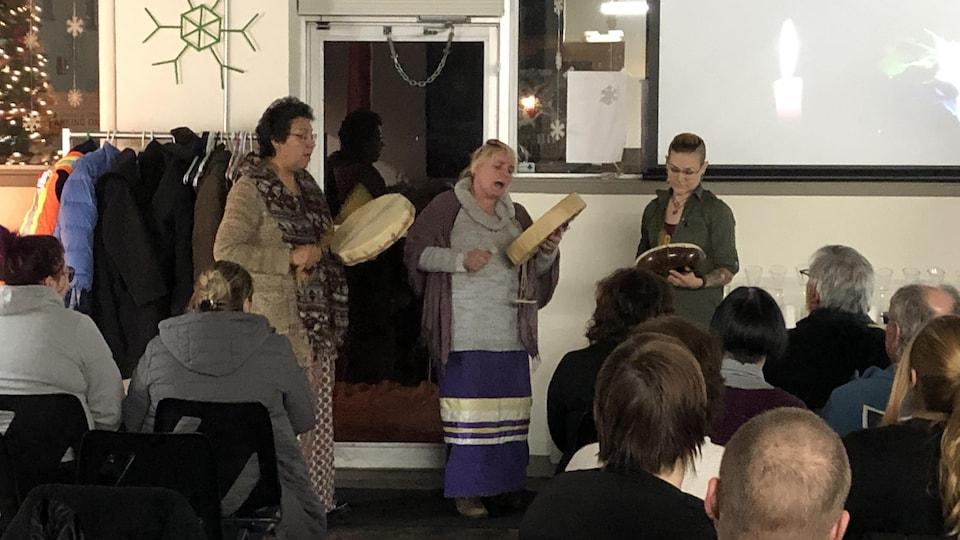 Des femmes jouant du tambours devant un petit groupe de personnes.