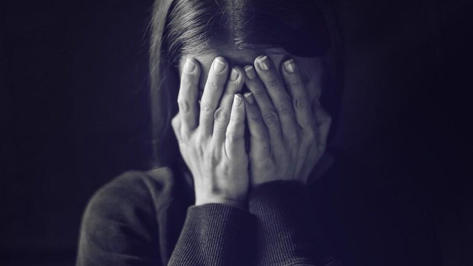 Une femme, la tête dans les mains.