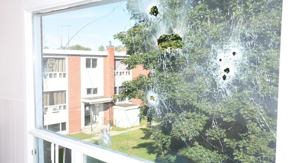 Une fenêtre avec des trous causés par une arme à feu.