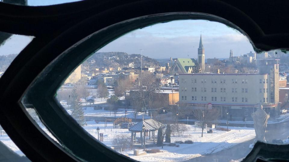 Une vue de la ville prise à travers une ouverture dans une rosace.