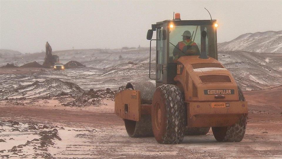 Un employé circule dans de l'équipement de machinerie lourde sur le site d'une mine de fer.