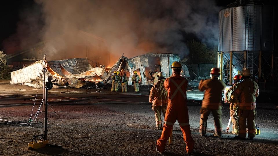 Des pompiers observent la ferme détruite.