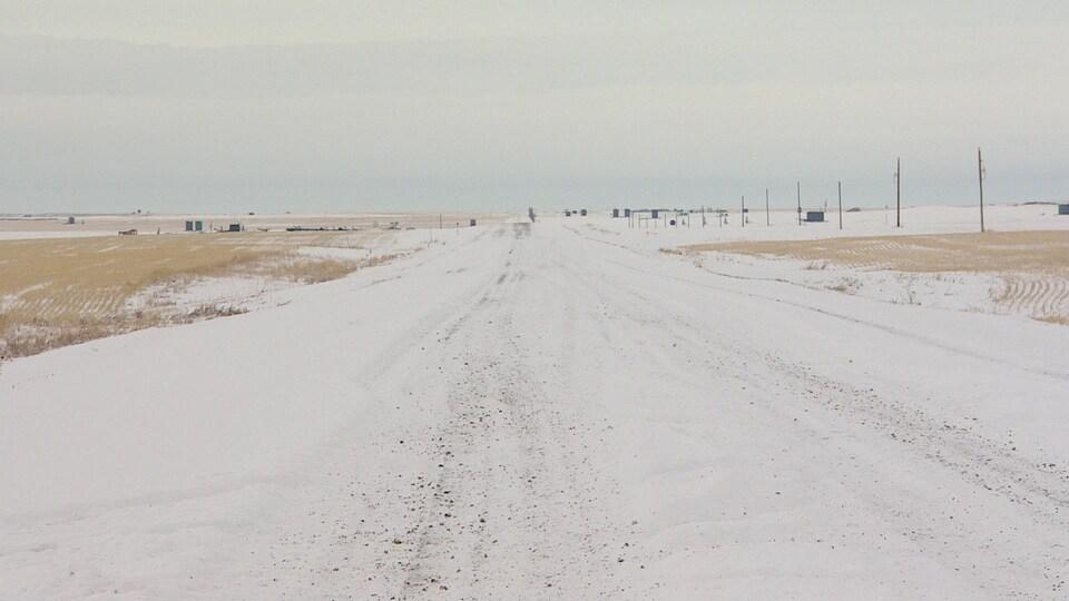 Une route enneigée au milieu de champs agricoles.