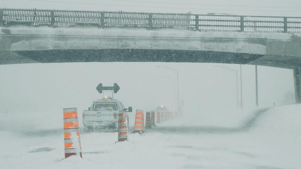 Un véhicule de la voirie assure la circulation sous un viaduc dans une tempête de neige.