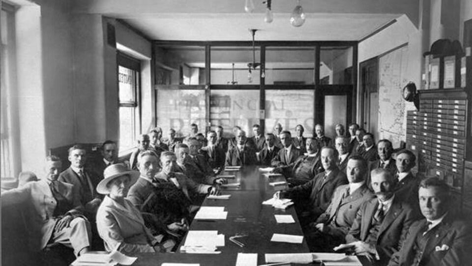 Une photo des années 20 avec des hommes en costume assis autour d'une grande table. Une seule femme est assise avec eux.