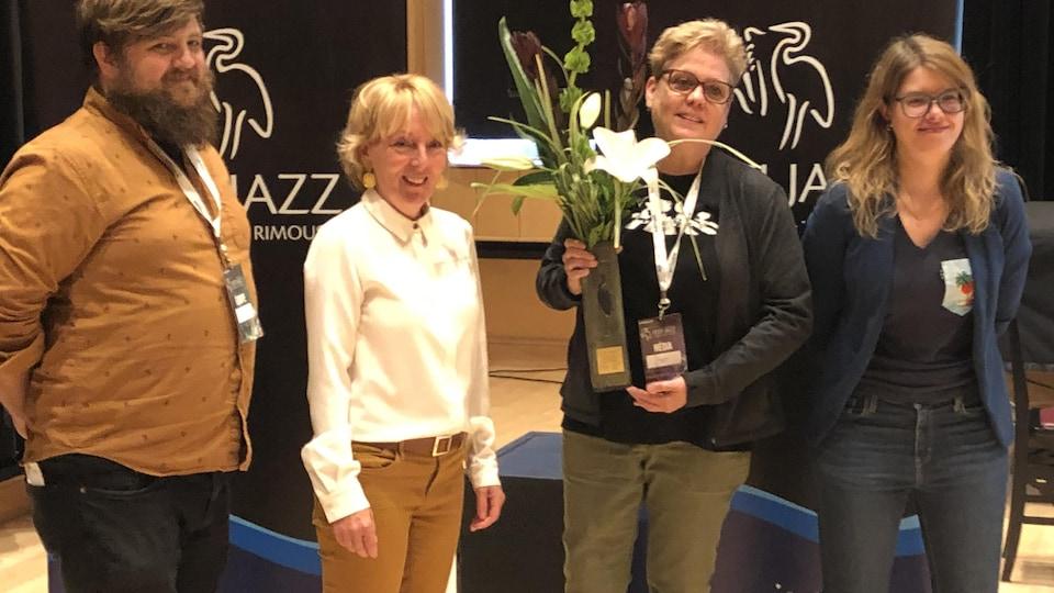 Colette Schryburt reçoit le prix Héron et pose en compagnie de trois autres personnes.