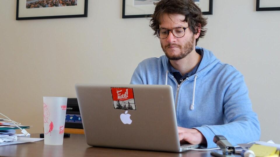 Clément Turgeon Thériault, directeur général et artistique du Festif de Baie-Saint-Paul, en train de travailler à son bureau.