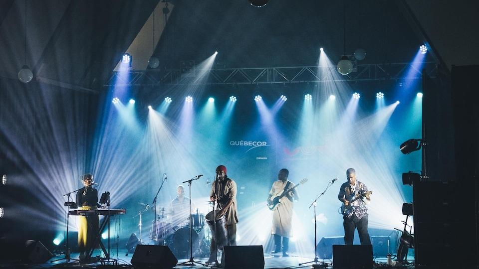 Cinq musiciens sur scène, en spectacle.