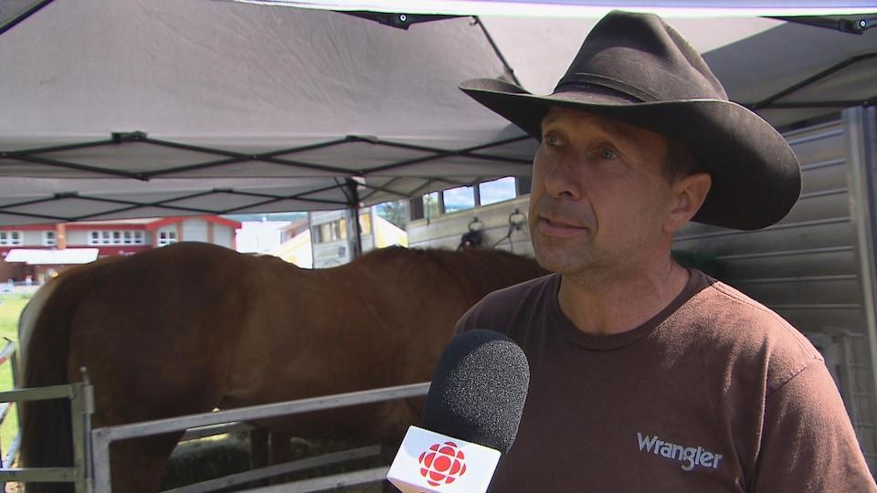 Il porte un large chapeau de cowboy noir durant l'entrevue.