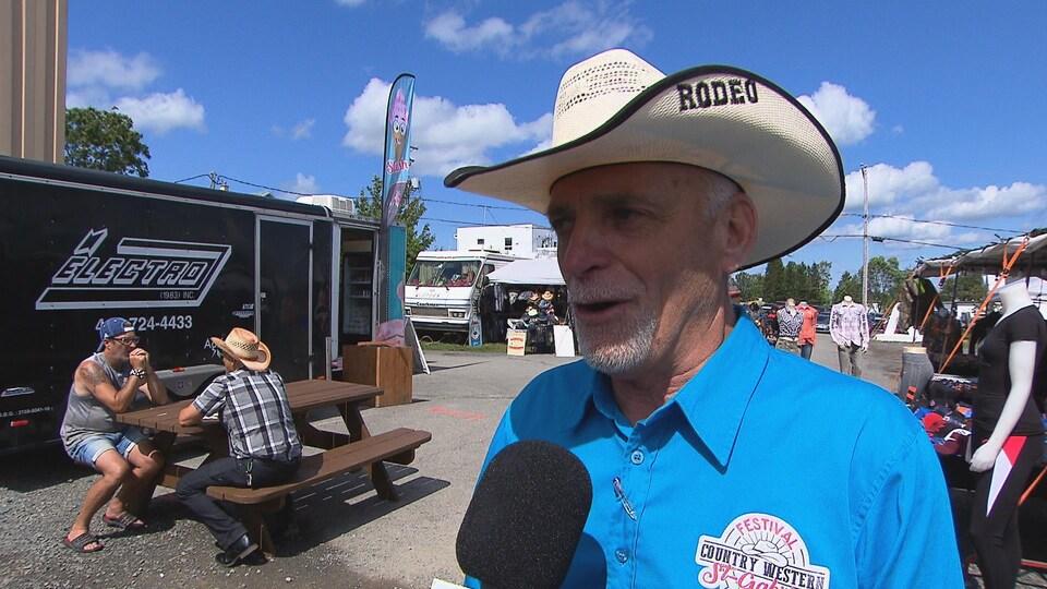Il porte le chandail avec le logo du festival et un chapeau de cowboy affichant la mention rodéo.