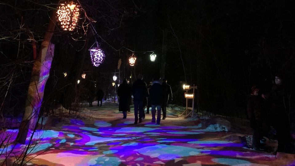 Des gens marchent dans un sentier enneigé éclairé par des lanternes multicolores.