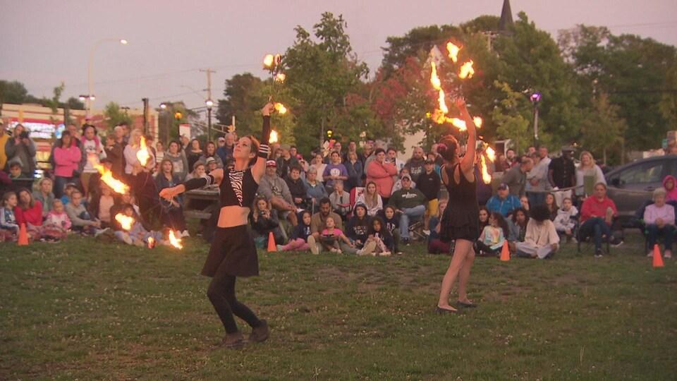 Des artistes dansent avec des cerceaux de feu devant un public.