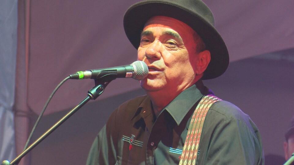 Il chante devant un micro.
