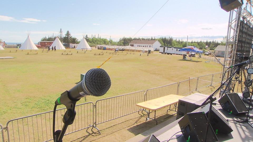 On retrouve notamment quelques tentes et des bancs derrière la zone en gazon à l'avant de la scène.
