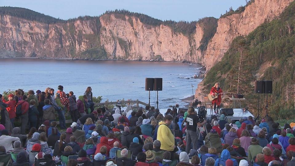 Plusieurs personnes assistent à un spectacle en plein air.
