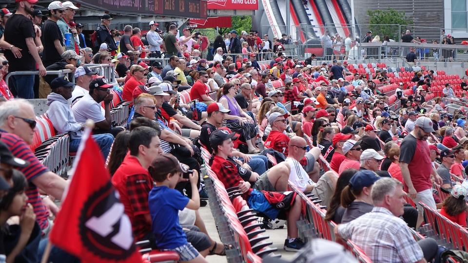 Une foule regardant des joueurs sur le terrain de la Place TD à Ottawa.
