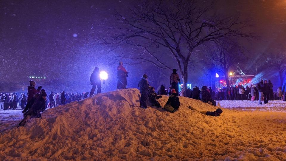 Des enfants sur une petite colline de neige devant la scène de la place de l'Assemblée nationale.