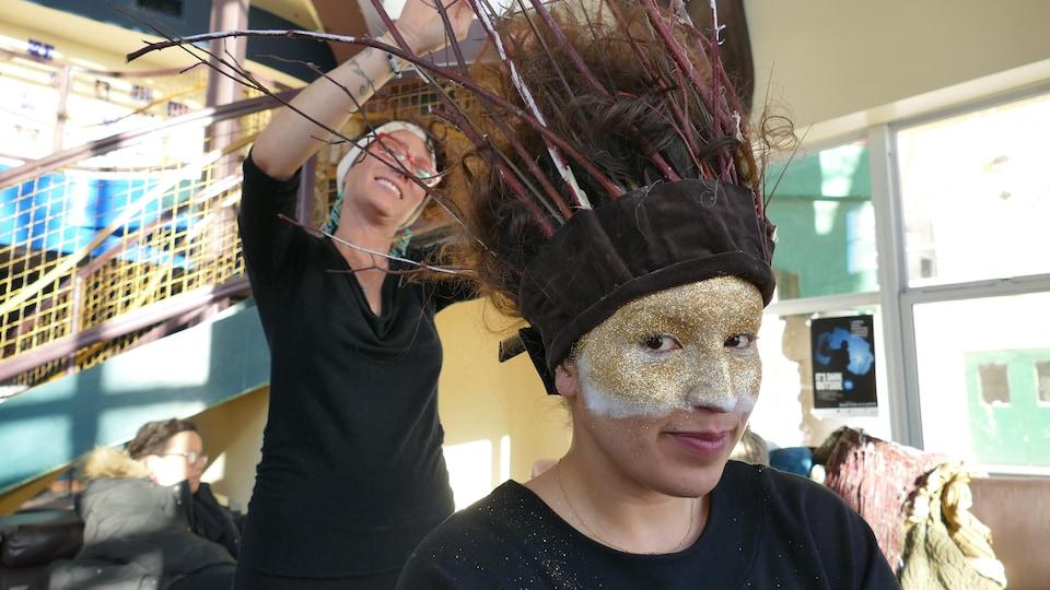 Un  mannequin assis sur une chaise au Festival du Voyageur attend qu'un designer lui installe des branches sur sa tête