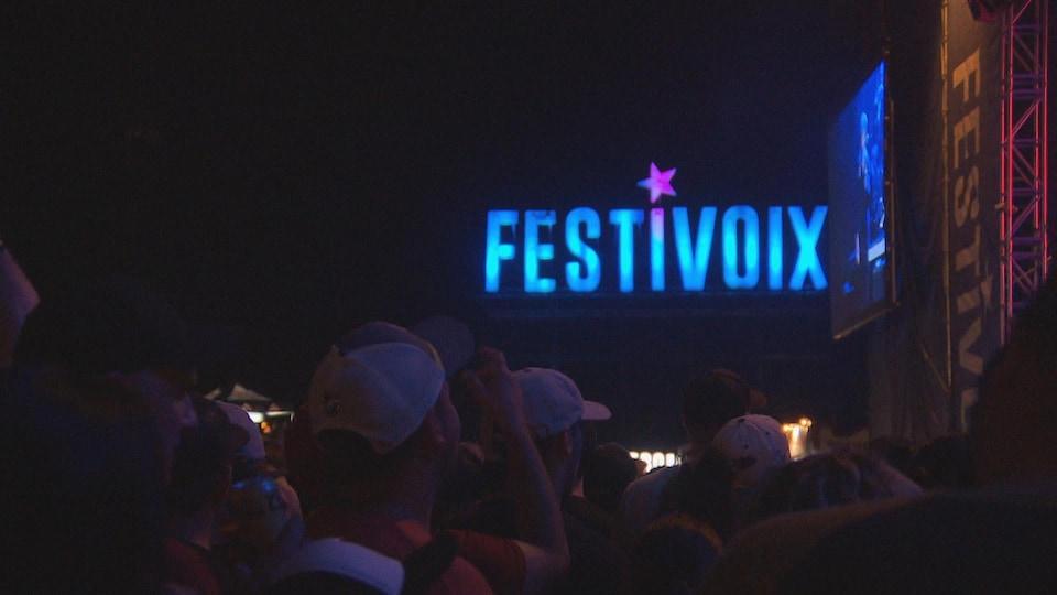 Gens qui regardent une scène avec les lettres du Festivoix en gros