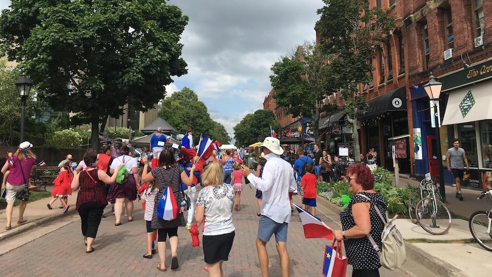 Des gens marchent sur Victoria Row, drapeaux dans les mains, en portant fièrement les couleurs de l'Acadie.