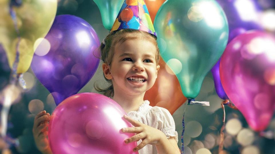 Une petite fille tient un ballon rose dans ses mains et est entourée des ballons gonflables de toutes les couleurs.