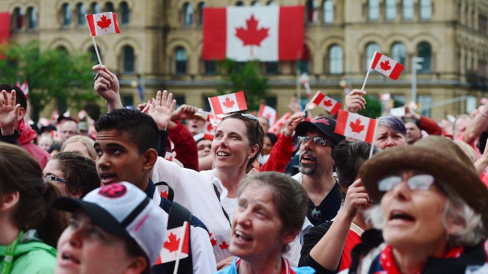 Une foule parmi laquelle plusieurs personnes tiennent des petits drapeaux du Canada.