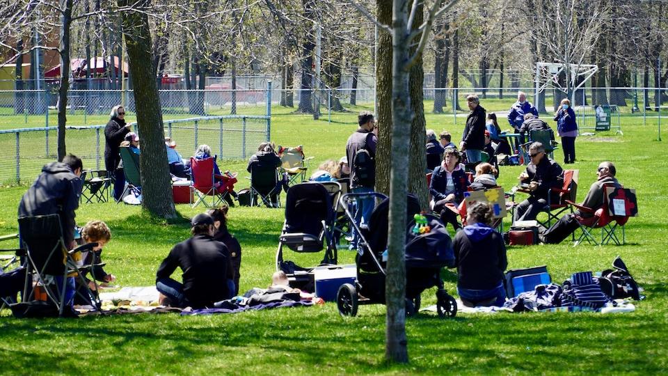 Des familles installées sur des couvertures dans un parc