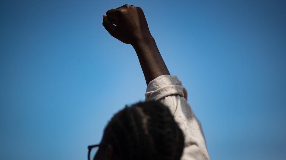 Une personne noire lève le poing en l'air.