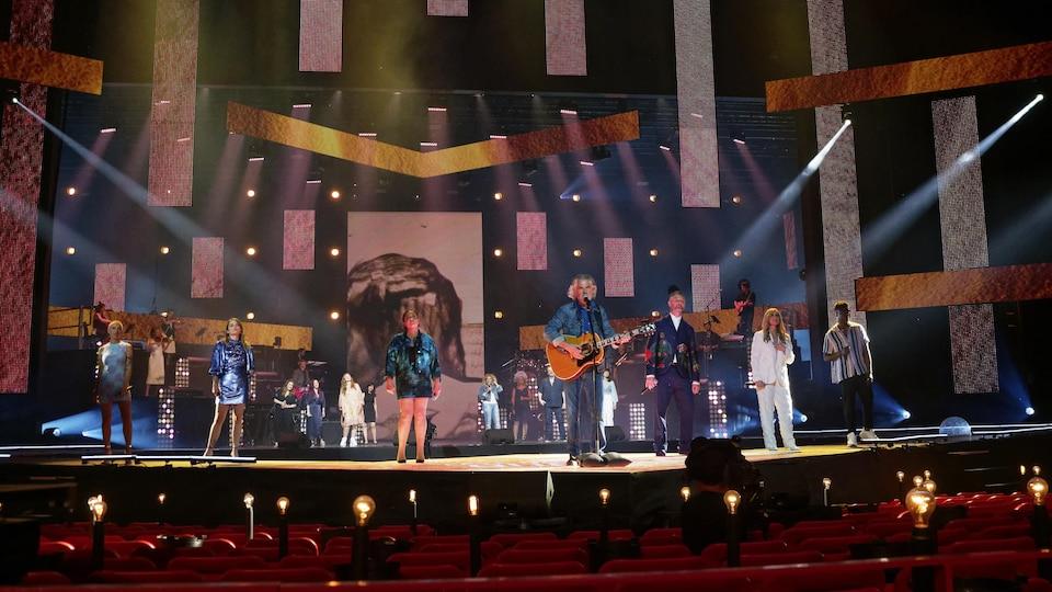Des artistes sur une scène sans public dans la salle.