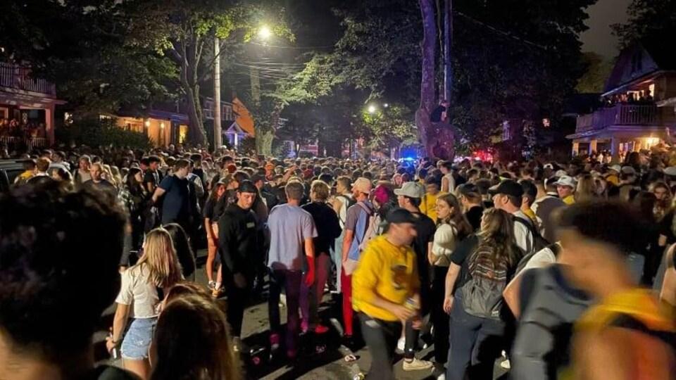 Des dizaines de personnes sont dans la rue, le soir.