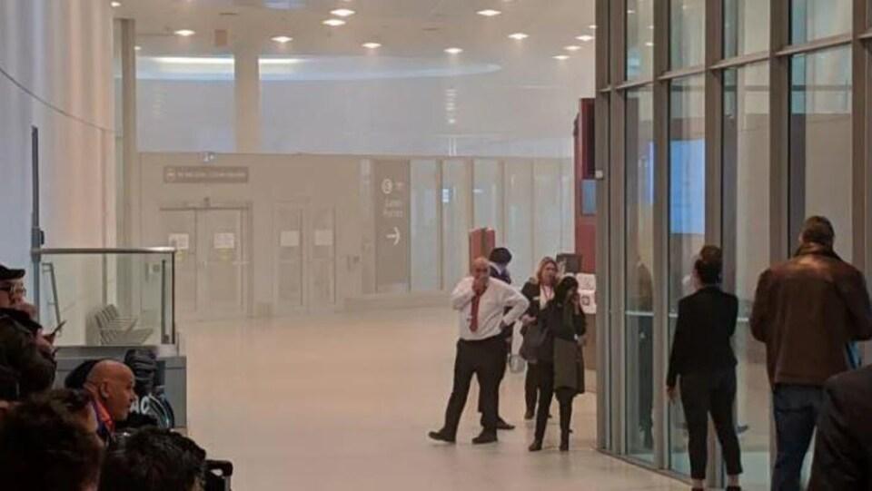 Des gens qui se protègent le visage de la fumée dans un corridor.