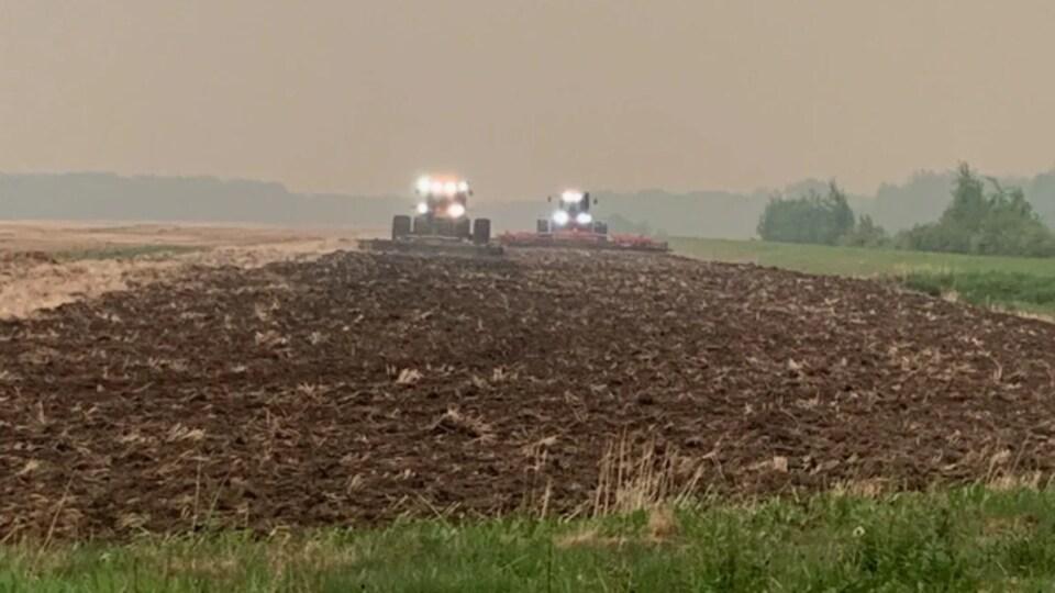 Les tracteurs labourent le champ près de High Level. Ils sont entourés de la fumée des feux de forêts.