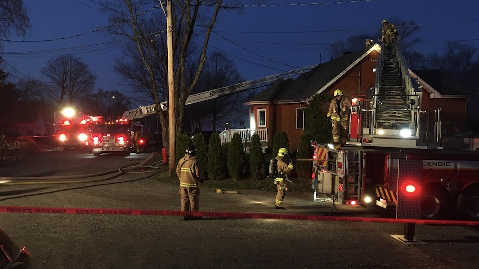 Des pompiers regardent la maison incendiée.