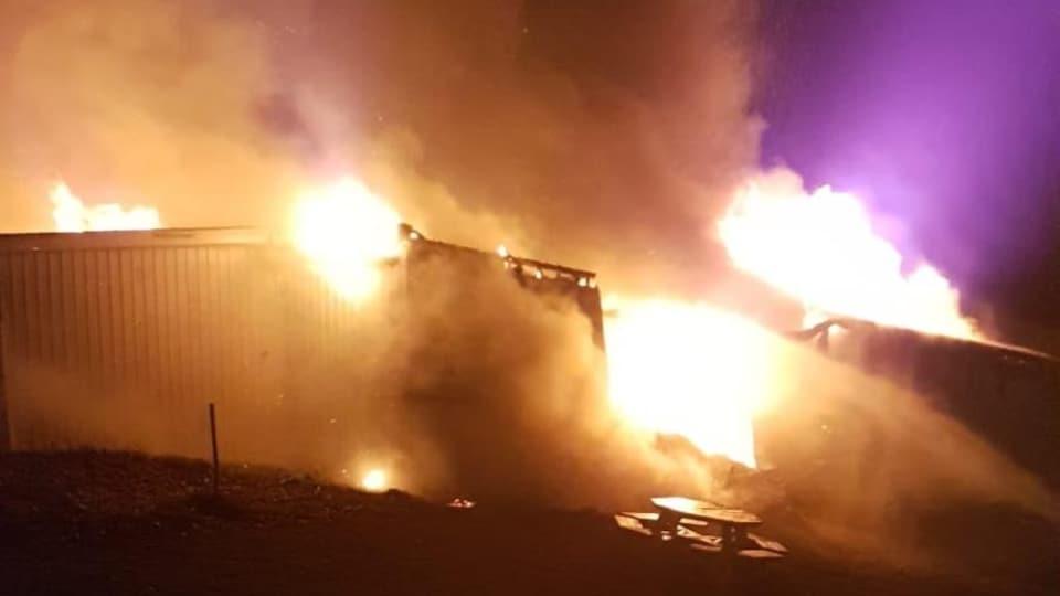 De grandes flammes sortent du toit de l'édifice