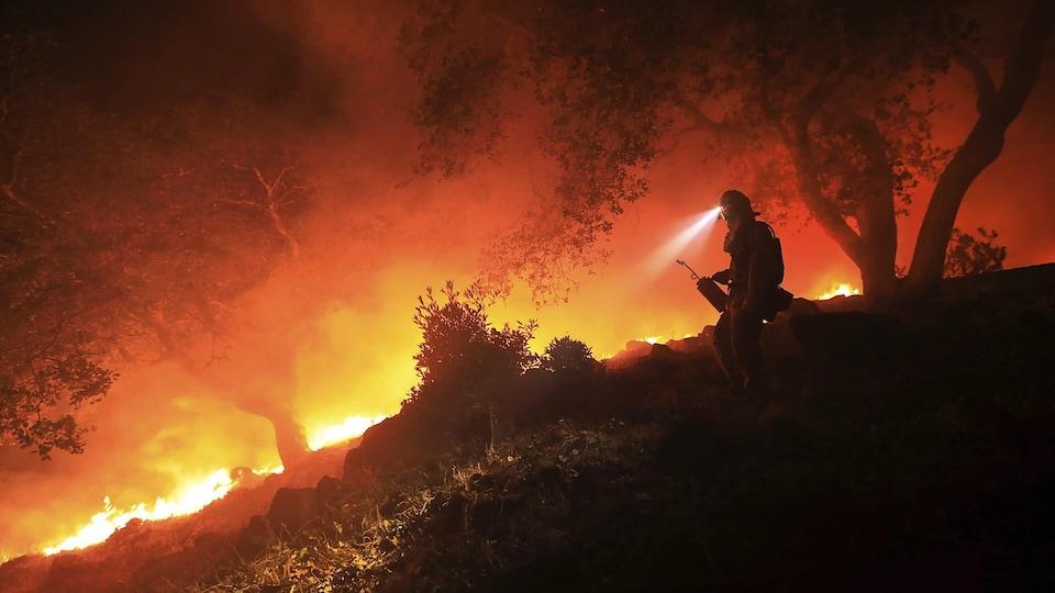 Un pompier équipé d'une lampe frontale dans une forêt en flammes