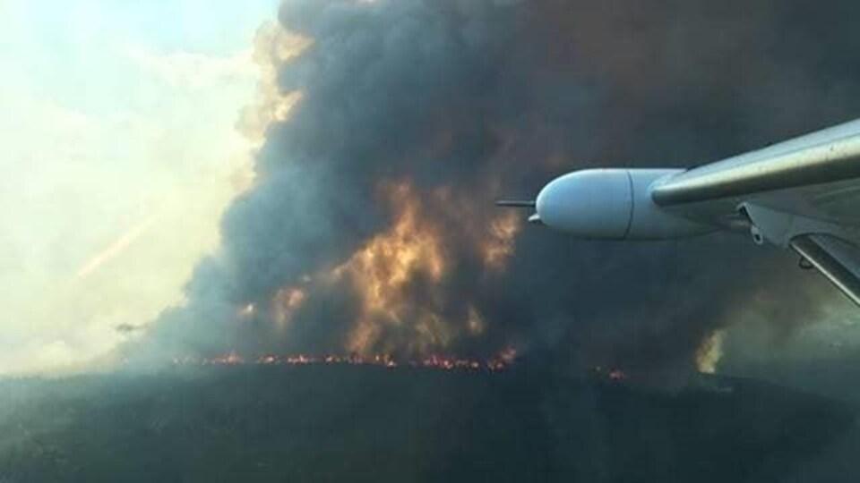 Photo de l'incendie prise d'un avion. De la fumée noire et très dense se dégage de l'incendie.