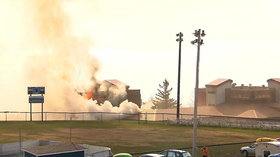 Flammes et fumées qui s'échappent d'un bâtiment.