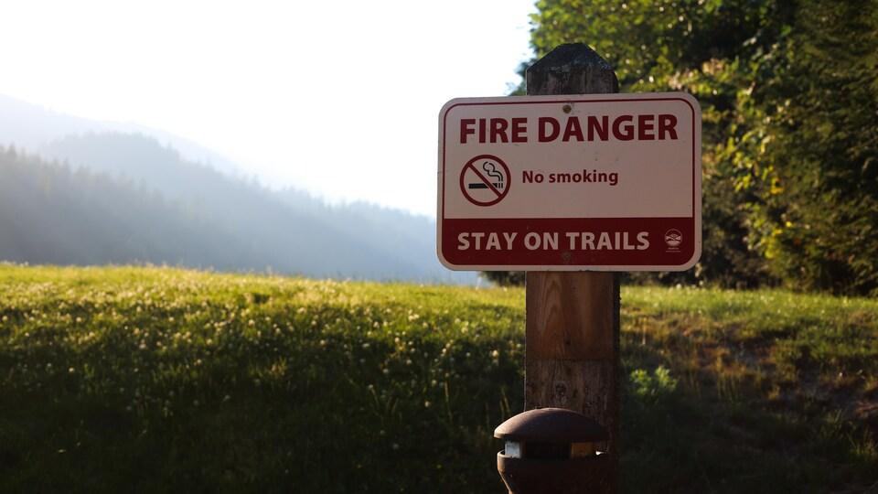 Une pancarte indique qu'il y a un danger de feu et demande aux visiteurs de demeurer sur les sentiers et de ne pas fumer.