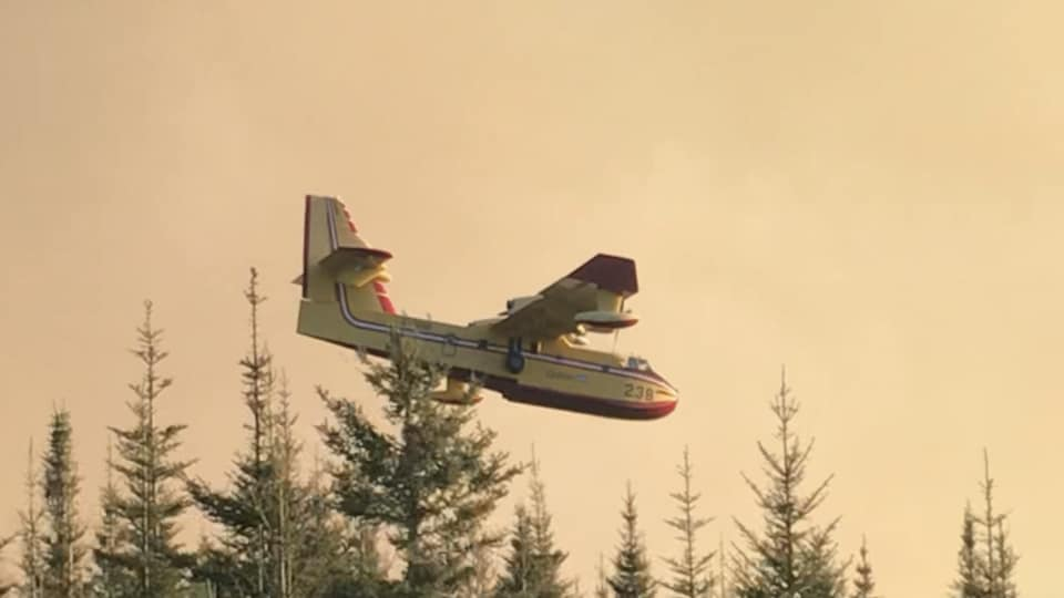 Un avion citerne de la SOPFEU survole le feu en Haute-Gaspésie.