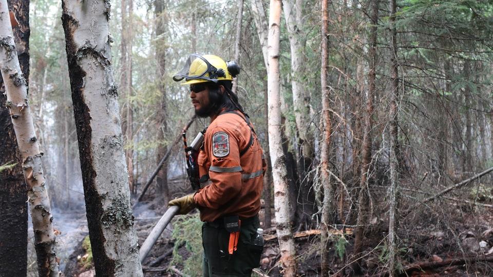 Un pompier éteint un feu de forêt.