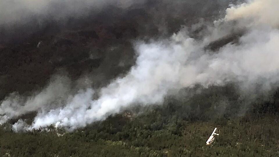 Vue aérienne de feux de forêt avec un hélicoptère à droite de la photo.