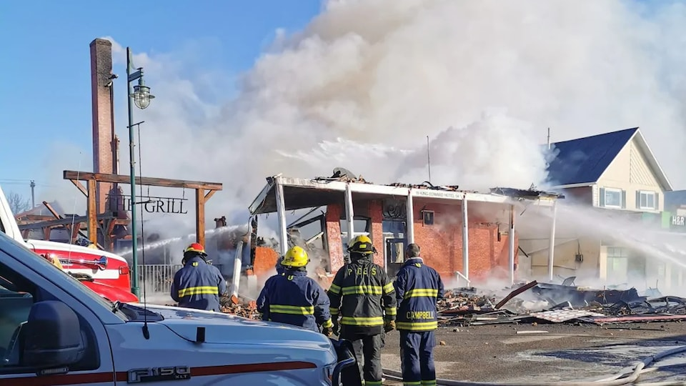 Un édifice complètement détruit par le feu. Des pompiers sont devant les décombres.