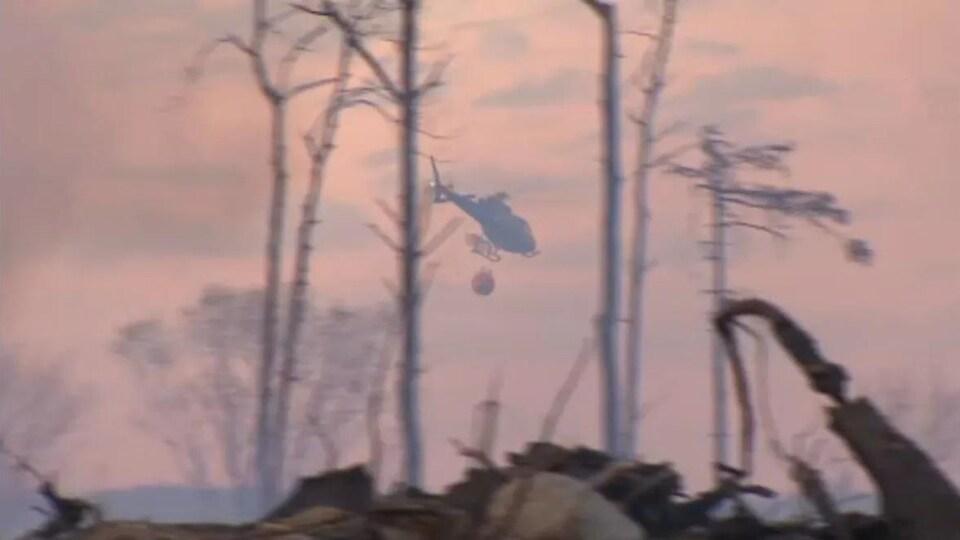 Un hélicoptère survole l'incendie.