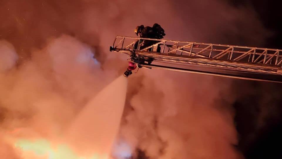 Un pompier installé dans une échelle arrose le toit du motel.