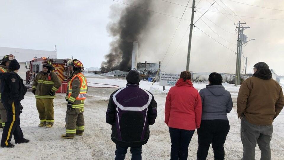 Des gens regardent la fumée qui se dégage encore de l'usine Cape Bald Packers à Richibouctou-Village.
